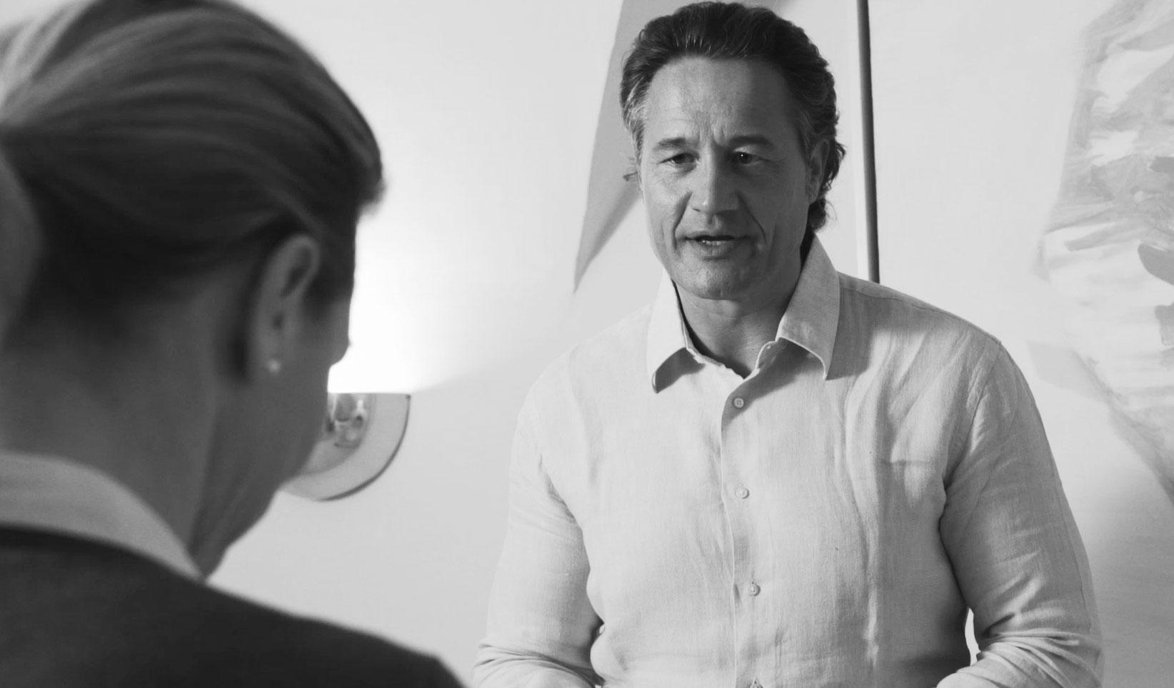 Van Haentjens spricht mit einer Dame, die mit dem Rücken zur Kamera gedreht ist